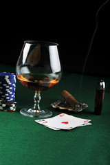 drink and playing cards on green
