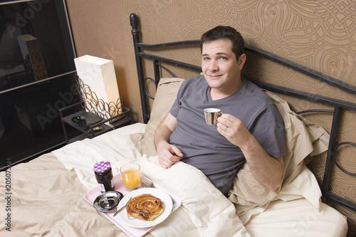 petit d jeuner au lit homme dans un h tel photo libre de droits sur la banque d 39 images. Black Bedroom Furniture Sets. Home Design Ideas