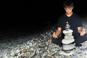 Keuken foto achterwand Boeddha teenager boy meditating near pyramid from pebble on seacoast