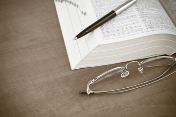 open book with a glasses and pen