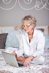 seniorin im schlafzimmer surft im internet