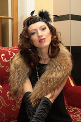 beautiful woman in evening gown and furs in the luxurious interi