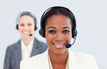 Ethnic businesswoman and her colleague with headset on