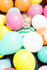Boy surrounded by baloons
