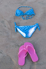 blue polka dot bikini on sand next to pink shoes, costa rica