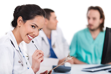 Young asian doctor smiling with the pen , others blurred behind