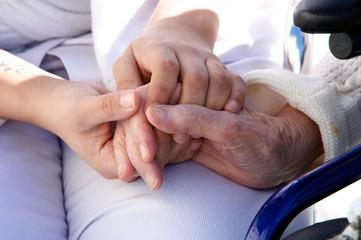 mains de personnel soignant assistant une personne agée