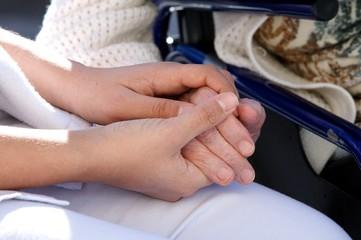 mains de jeune soignante assistant une personne agée