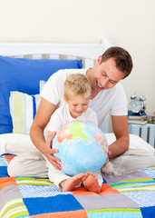 Laughing father and his son looking at a terrestrial globe