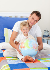 Father and son looking at a terrestrial globe