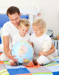 Cute siblings and their father looking at a terrestrial globe