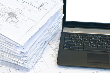 Laptop near pile of project drawings