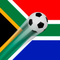 Ein fliegender Fußball vor der Flagge von Südafrika