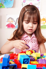 Child with  block and construction set in play room.