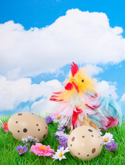 a colorful chicken and two dotted easter eggs between flowers in