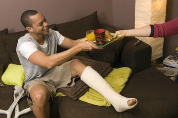 Homme jambe cassé prends son petit déjeuner
