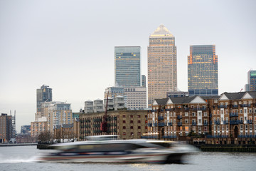 Fast boat on Thames, London, UK, with Canary Wharf in background