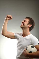 junger mann hält einen Fussball und hebt den arm