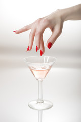 Beautiful hand with perfect red manicure holding martini glass