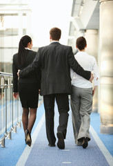 group of three persons talking on the corridor in office space,