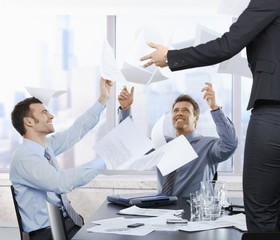 Businessmen throwing documents up