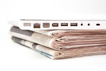 Stapel Zeitungen mit Laptop oben drauf