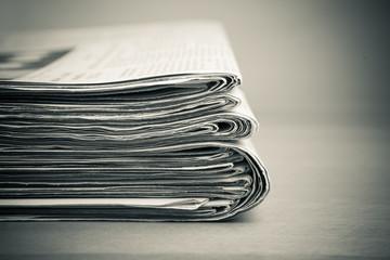 Stapel Zeitungen auf Holztisch, monochrom