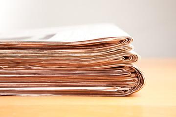 Stapel Zeitungen auf Holztisch