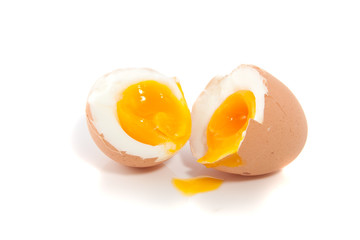 a soft boiled egg cut in two halves isolated on white