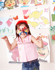 Child with paint of face in play room.