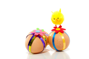 three colorful decorated easter eggs with a yellow chick on top