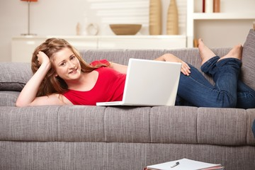 Smiling teen with laptop on sofa at home