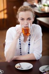 junge frau trinkt tee im cafe