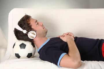 junger mann mit kopfhörern hört musik und liegt auf fussball