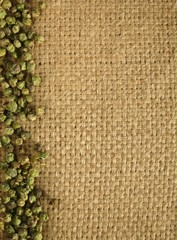 Pepper grains on natural burlap background