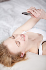 junge frau schreibt im bett eine sms