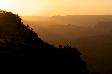People on Bluff Amid Silhouetted Hills
