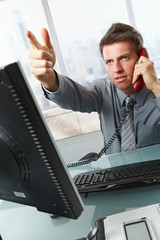 Businessman calling and gesturing in office