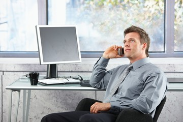 Businessman on call sitting at desk looking up