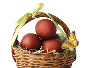 Red dyed eggs and a butterfly in a basket