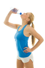 Thirsty young women drinking water after fitness workout