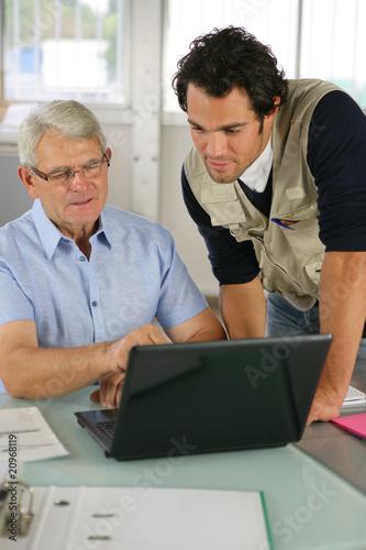 portrait de deux hommes au bureau devant un ordinateur. Black Bedroom Furniture Sets. Home Design Ideas