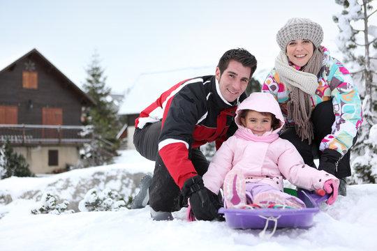 Famille faisant de la luge à la neige