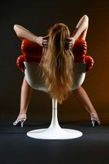 Frau lässt lange rote Haare über Sessel hängen
