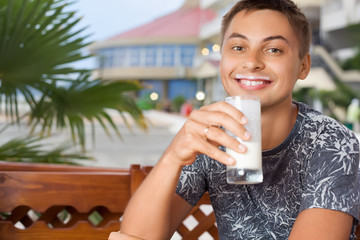 young smiling man sitting in an arbour on resort, drinking kefir