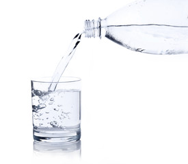 Water, flows from a plastic bottle in a glass isolated on white