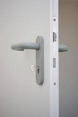 weiße offene Holztür mit Schlüssel