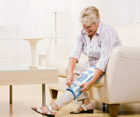Senior woman adjusting knee brace