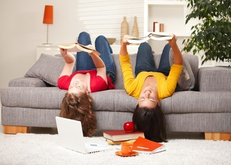 Girls reading upside down on sofa