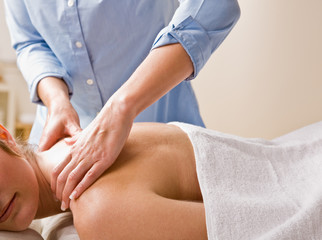 Massage therapist giving woman massage